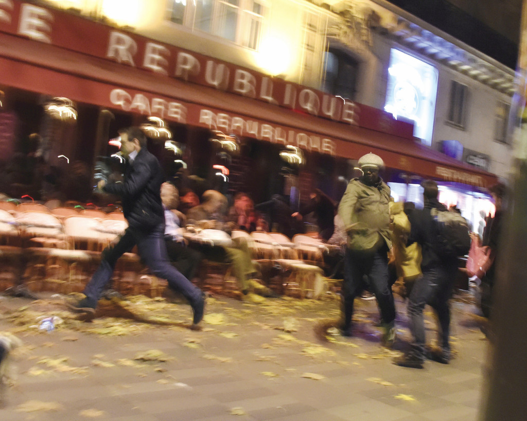 People run after hearing what is believed to be explosions or gun shots near Place de la Republique in Paris on November 15, 2015. Above: Rescuers evacuate an injured person near the Bataclan concert hall in central Paris, November 14, 2015. Photo: Dominique Faget/AFP Images